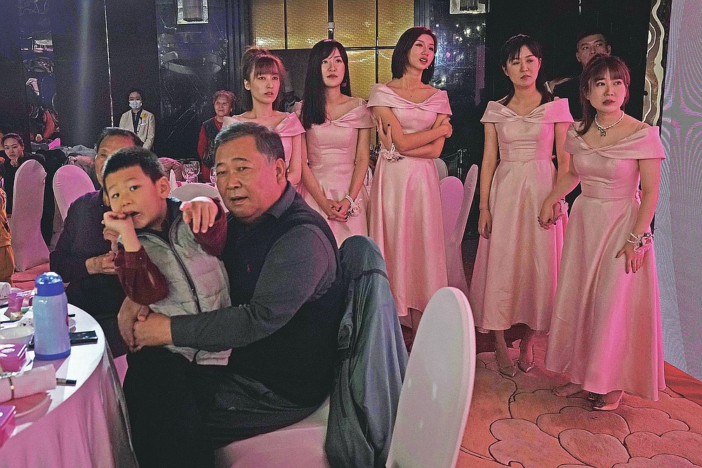 Bridesmaids gather during a wedding banquet in Beijing on Saturday, Dec. 12, 2020. Lovebirds in China are embracing a sense of normalcy as the COVID pandemic appears to be under control in the country where it was first detected. (AP Photo/Ng Han Guan)