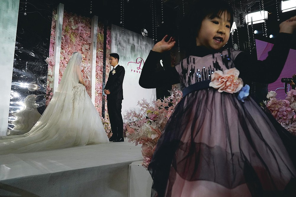 A child reacts as bride Chen Yaxuan and groom Dou Di exchange vows during an unmasked wedding banquet in Beijing on Saturday, Dec. 12, 2020. Lovebirds in China are embracing a sense of normalcy as the COVID pandemic appears to be under control in the country where it was first detected. (AP Photo/Ng Han Guan)