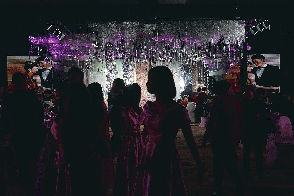 Guests attend an unmasked wedding banquet in Beijing on Saturday, Dec. 12, 2020. Lovebirds in China are embracing a sense of normalcy as the COVID pandemic appears to be under control in the country where it was first detected. (AP Photo/Ng Han Guan)