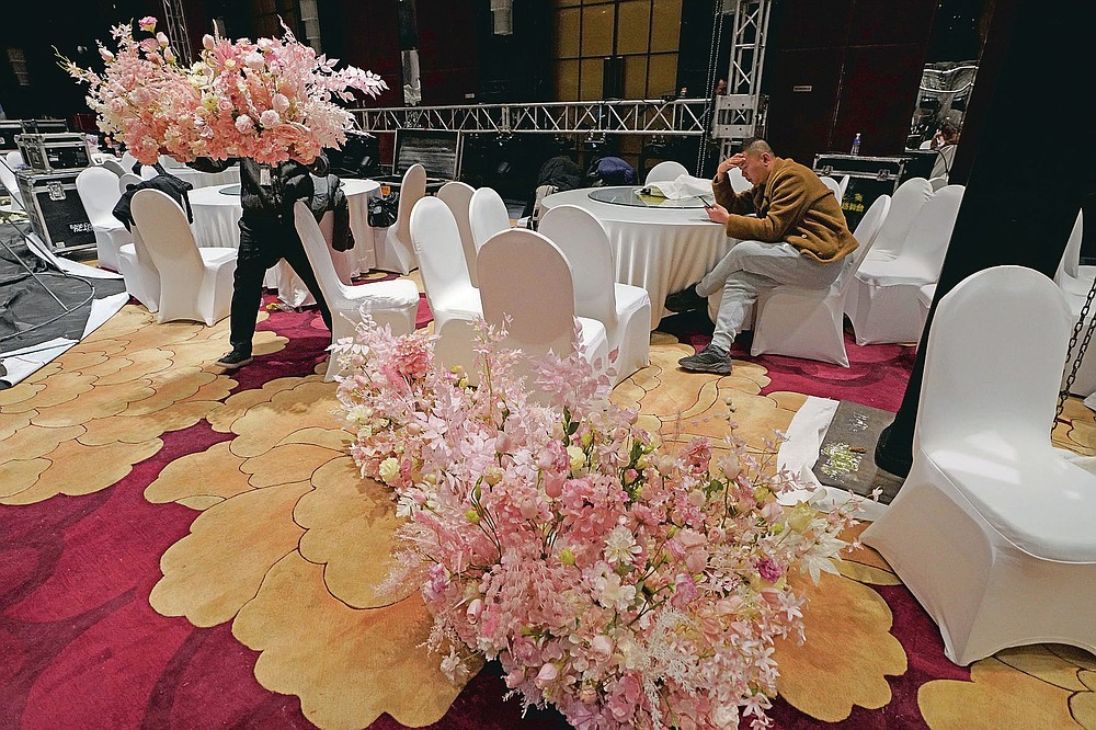 Workers from a wedding planner company set up decorations a day before an unmasked wedding banquet in Beijing on Friday, Dec. 11, 2020. The wedding planner reported 50% decrease in business over the previous year but is optimistic for the future as couples who pushed back their weddings are helping revitalize the industry as the pandemic fades and restrictions are lifted in China. (AP Photo/Ng Han Guan)