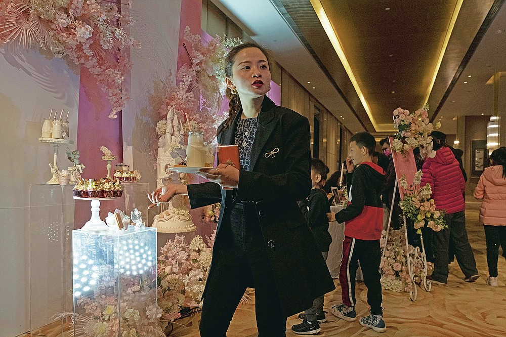 Ning Jingyuan, a wedding planner, supervises the setup for an unmasked wedding banquet in Beijing on Saturday, Dec. 12, 2020. The wedding planner reported 50% decrease in business over the previous year but is optimistic for the future as couples who pushed back their weddings are helping revitalize the industry as the pandemic fades and restrictions are lifted in China. (AP Photo/Ng Han Guan)