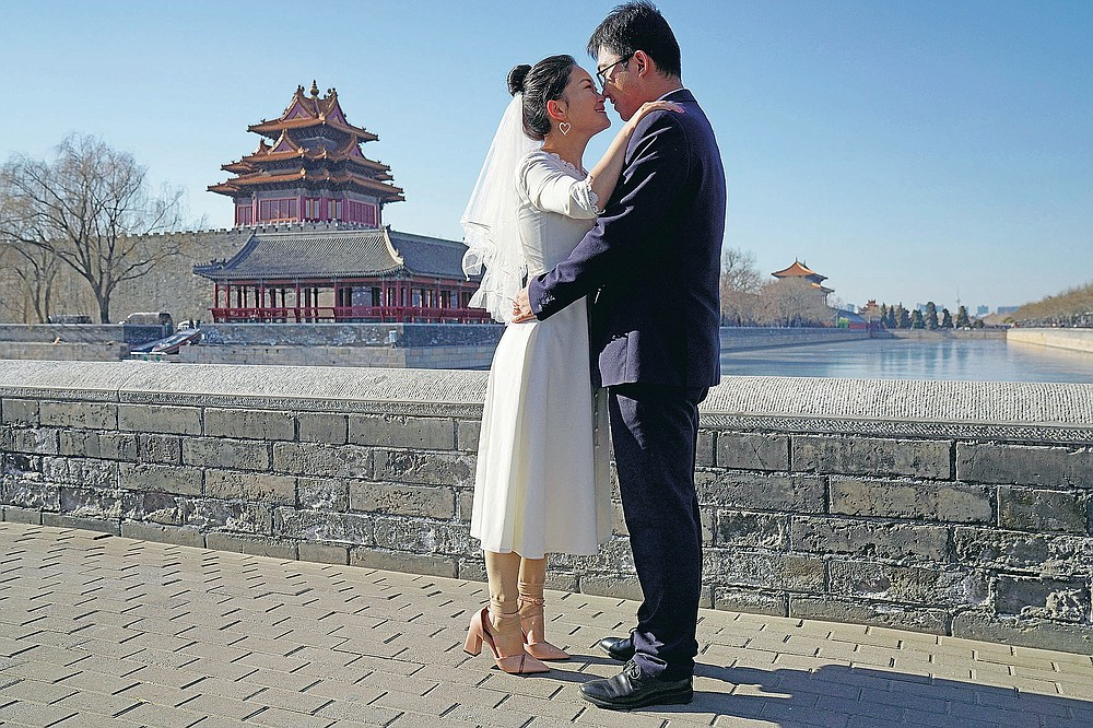 Groom Dong Yangfeng and bride Wang Sai pose for photos near the Forbidden City in Beijing on Sunday, Dec. 20, 2020. Lovebirds in China are embracing a sense of normalcy as the COVID pandemic appears to be under control in the country where it was first detected. (AP Photo/Ng Han Guan)