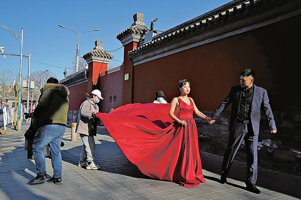 A couple has their wedding photos taken near the Forbidden City area in Beijing on Sunday, Dec. 20, 2020. Lovebirds in China are embracing a sense of normalcy as the COVID pandemic appears to be under control in the country where it was first detected. (AP Photo/Ng Han Guan)