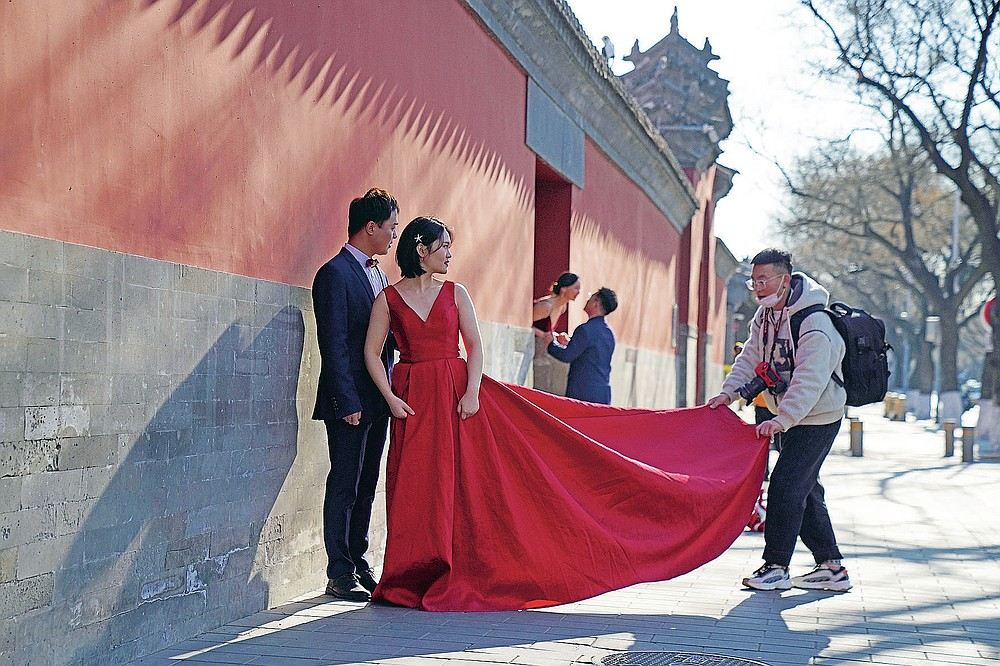 Couples have their wedding photos taken near the Forbidden City area in Beijing on Sunday, Dec. 20, 2020. Lovebirds in China are embracing a sense of normalcy as the COVID pandemic appears to be under control in the country where it was first detected. (AP Photo/Ng Han Guan)