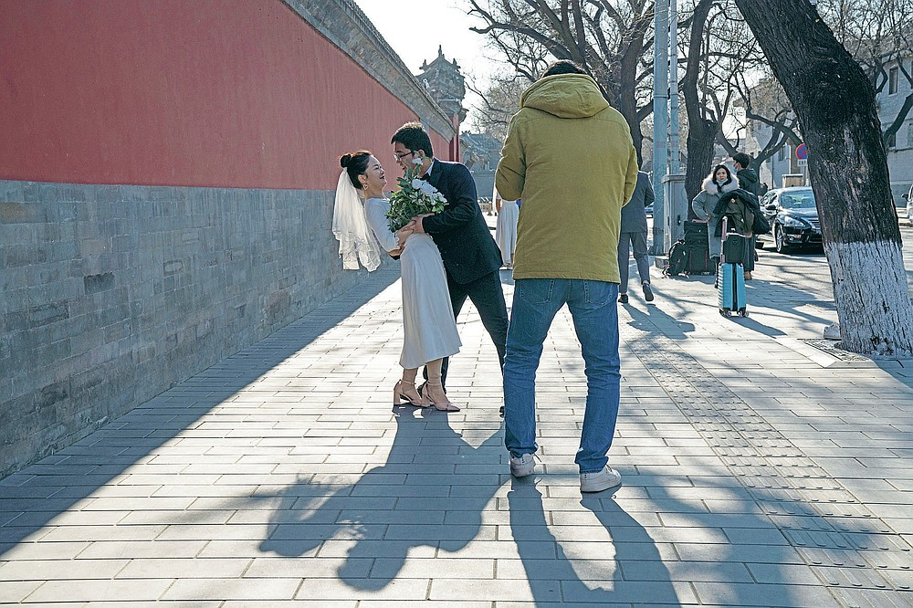Groom Dong Yangfeng and bride Wang Sai pose for photos near the Forbidden City in Beijing Sunday, Dec. 20, 2020. Lovebirds in China are embracing a sense of normalcy as the COVID pandemic appears to be under control in the country where it was first detected. (AP Photo/Ng Han Guan)