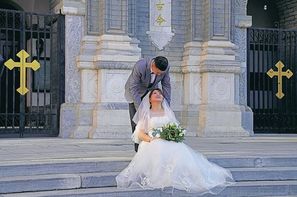 A couple has their wedding photos taken outside the Wangfujing church in Beijing on Friday, Dec. 25, 2020. Lovebirds in China are embracing a sense of normalcy as the COVID pandemic appears to be under control in the country where it was first detected. (AP Photo/Ng Han Guan)