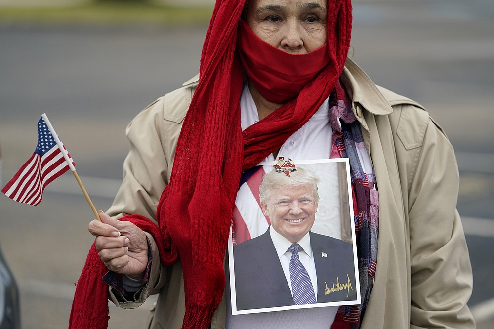 Tina Puente wears a portrait of President Donald Trump as she gathers with other supporters in anticipation of his visit to the U.S.-Mexico border, Tuesday, Jan. 12, 2021, in Harlingen, Texas. (AP Photo/Eric Gay)
