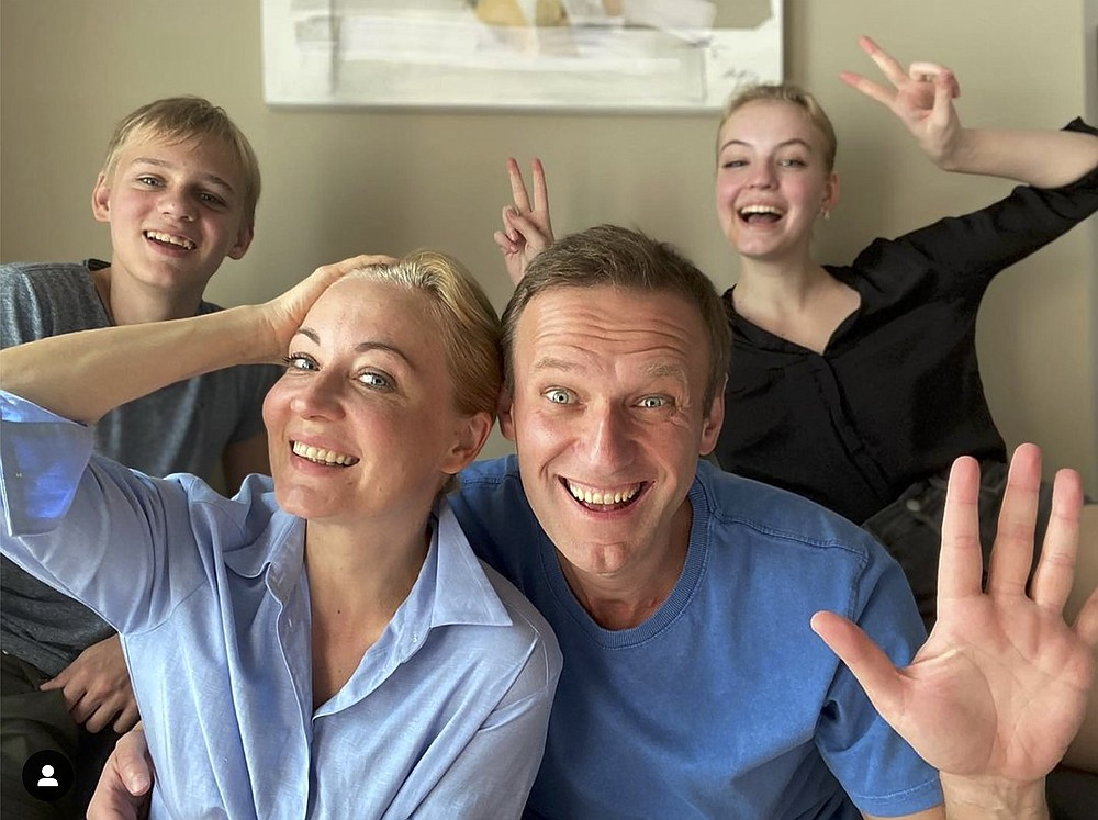 In this image taken from a video released on Dec. 31, 2020 by Russian opposition activist Alexei Navalny on his Instagram account, Russian opposition activist Alexei Navalny, foreground right, his wife Yulia, foreground left, his daughter Daria, right, and son Zakhar pose for a selfie. Russia's prison service has asked a Moscow court to put top Kremlin critic Alexei Navalny behind bars for breaching the terms of his suspended sentence and probation. Navalny, who is convalescing in Germany from an August poisoning with a nerve agent that he has blamed on the Kremlin, alleged Tuesday Jan. 12, 2021, that Russian President Vladimir Putin was behind the new legal motion. (Navalny instagram account via AP)
