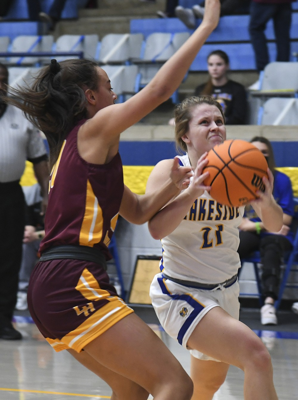 Lakeside's Erika Bittinger (21) goes for a basket as Lake Hamilton's Audri Winfrey (20) defends during Tuesday's game at Lakeside Athletic Complex. - Photo by Grace Brown of The Sentinel-Record
