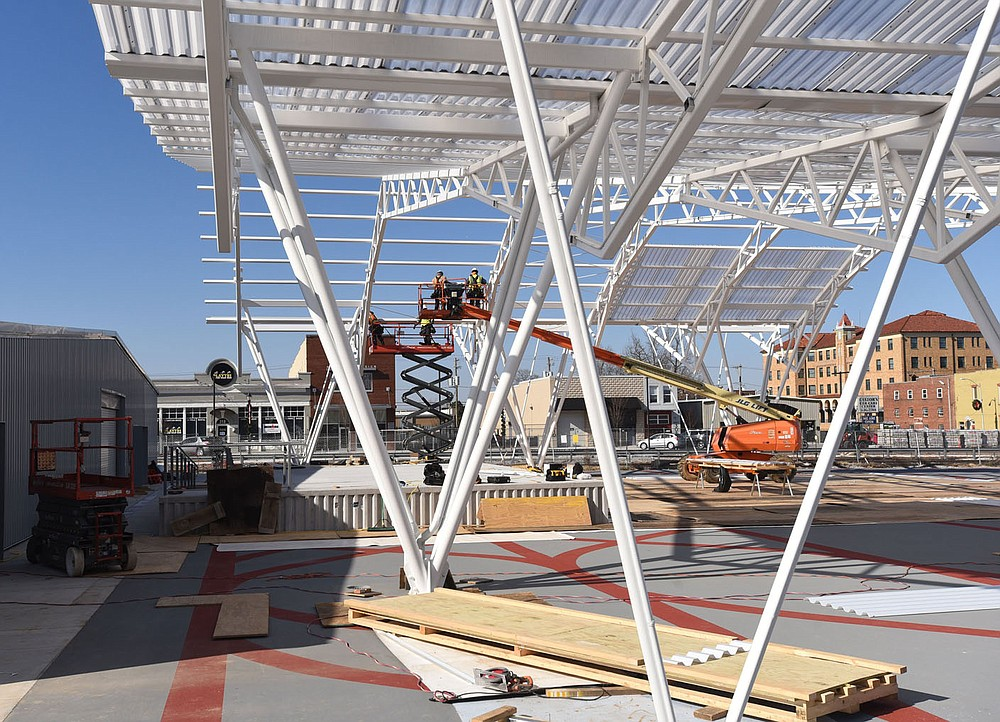 Workers make progress Tuesday on a canopy over a performance stage at Rail Yark Park in downtown Rogers. Go to nwaonline.com/210113Daily/ to see more photos. (NWA Democrat-Gazette/Flip Putthoff)