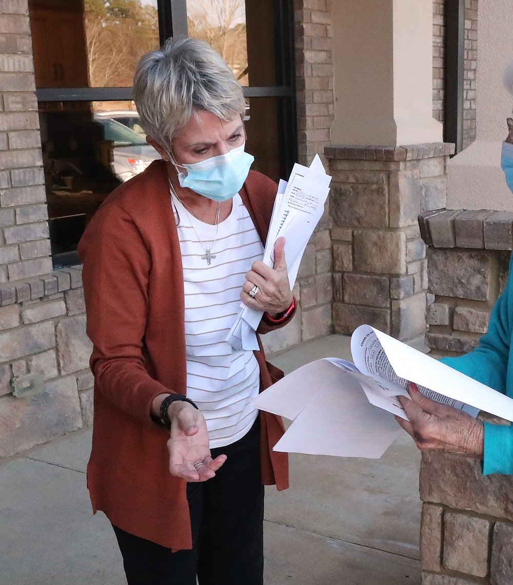 Oaklawn Center on Aging Executive Director Kathy Packard accepts some COVID-19 vaccine applications at the agency's offices Wednesday. - Photo by Richard Rasmussen of The Sentinel-Record