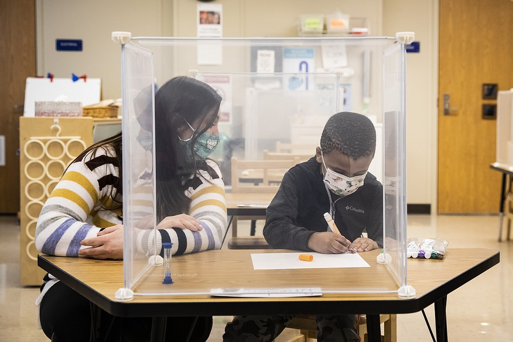 Pre-kindergarten teacher Sarah McCarthy works with a student at Dawes Elementary in Chicago, Monday, Jan. 11, 2021. Chicago Public Schools students began their return to the classroom Monday as school doors opened to thousands of pre-kindergarten and some special education students after going remote last March due to the coronavirus pandemic. (Ashlee Rezin Garcia/Chicago Sun-Times via AP, Pool)