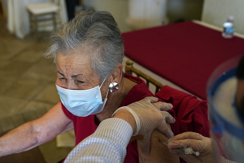 Resident Gail Nanning, 83, receives the Pfizer-BioNTech COVID-19 vaccine at the The Palace assisted living facility, Tuesday, Jan. 12, 2021, in Coral Gables, Fla. (AP Photo/Lynne Sladky)