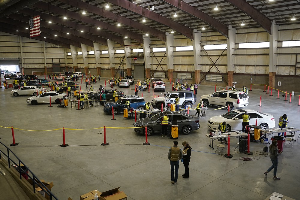 Cars pull in to nursing stations for the COVID-19 vaccine roll out at the Davis County Legacy Center Tuesday, Jan. 12, 2021, in Farmington, Utah. (AP Photo/Rick Bowmer)