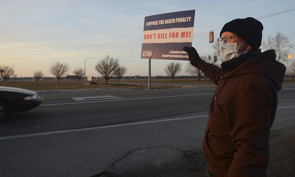 Death penalty opponent Wes Janz, of Indianapolis, holds up a sign for passing motorists to read as he and others protest the scheduled execution of Lisa Montgomery, Tuesday, Jan. 12, 2021, near the Federal Correctional Complex in Terre Haute, Ind. An appeals court granted a stay of execution Tuesday for Montgomery, convicted of killing a pregnant woman and cutting the baby from her womb in the northwest Missouri town of Skidmore in 2004. (Joseph C. Garza/The Tribune-Star via AP)