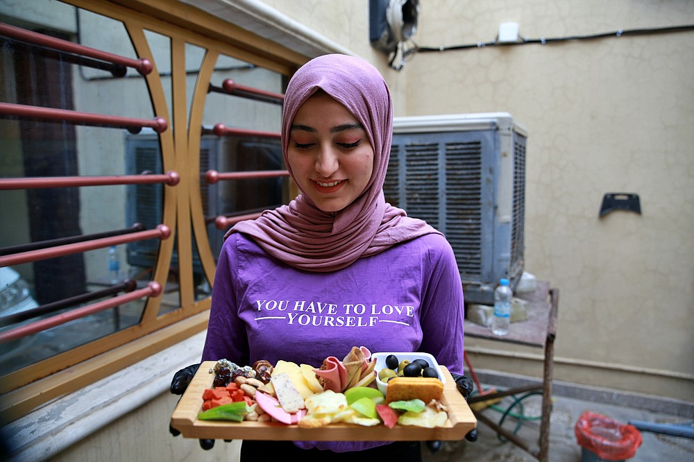 Fatima Ali shows her takeaway cheese-plate that she sells making a small but steady income, in Baghdad, Iraq, Saturday, Nov. 28, 2020. After Iraq imposed a coronavirus lockdown in March, Fatima is among a growing numbers of Iraqi women who are finding some good under the movement restrictions imposed because of the pandemic: They're starting their own businesses from home. (AP Photo/Khalid Mohammed)
