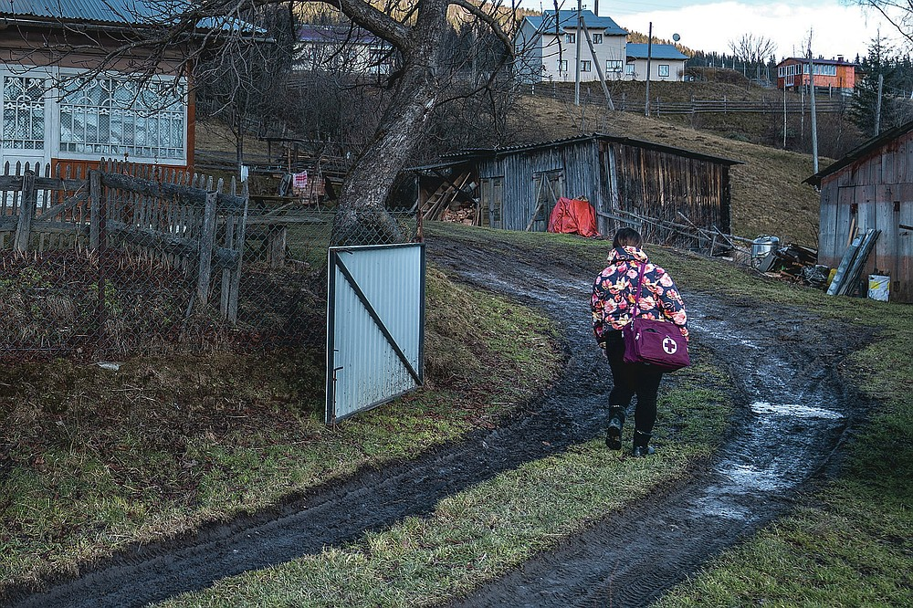 Dr. Viktoria Mahnych, walks on country road to attend to her patient near Iltsi village, Ivano-Frankivsk region of Western Ukraine, Wednesday, Jan. 6, 2021. Ukraine is struggling to contain the coronavirus pandemic that has inundated its overburdened medical system, as Dr. Viktoria Mahnych goes door to door providing much needed help to patients. (AP Photo/Evgeniy Maloletka)
