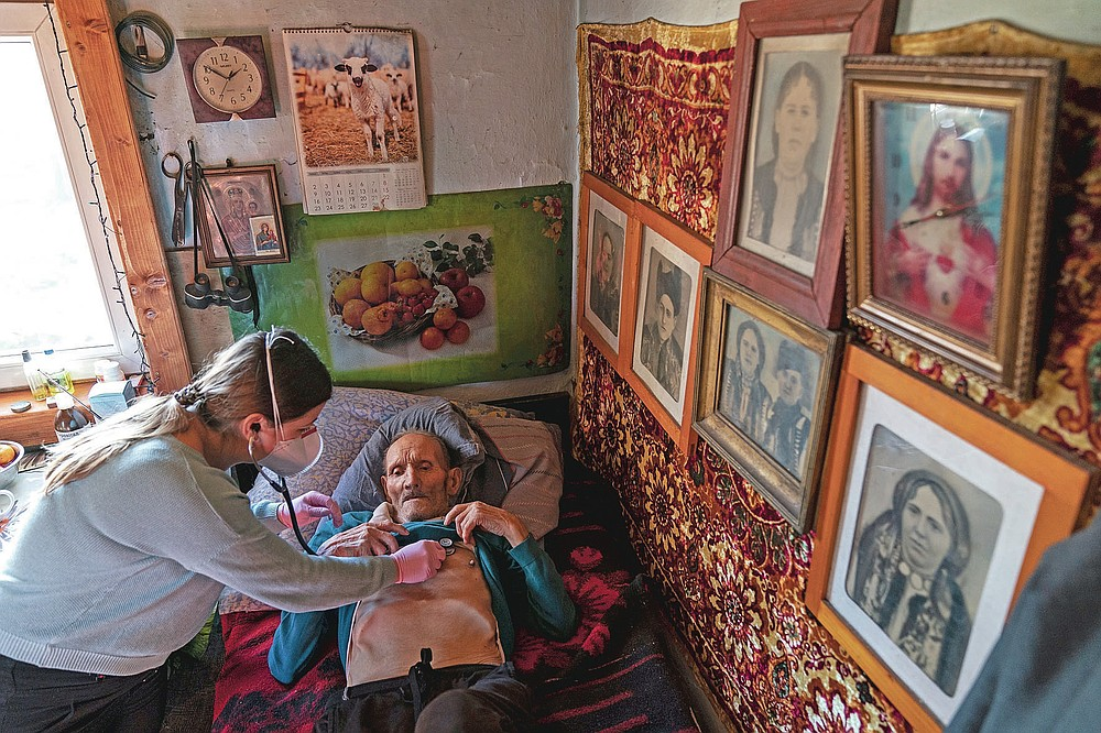 Dr. Viktoria Mahnych, wearing face mask against coronavirus, checks on a COVID-19 patient with a stethoscope at at his home in Iltsi village, Ivano-Frankivsk region of Western Ukraine, Wednesday, Jan. 6, 2021. Ukraine is struggling to contain the coronavirus pandemic that has inundated its overburdened medical system, as Dr. Viktoria Mahnych goes door to door providing much needed help to patients.(AP Photo/Evgeniy Maloletka)