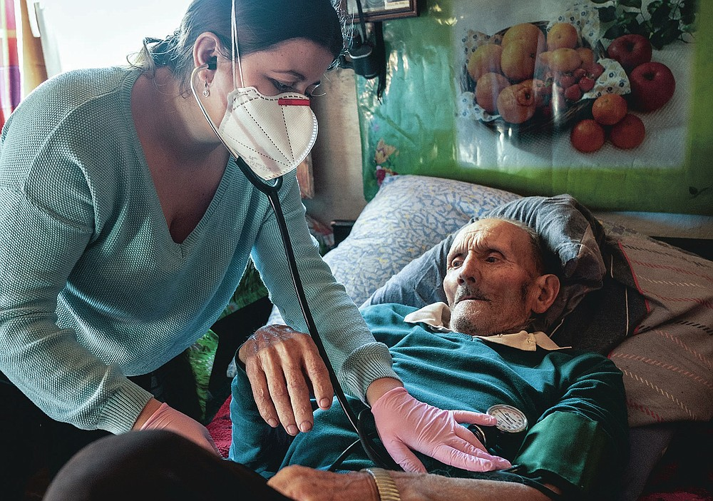 Dr. Viktoria Mahnych, wearing face mask against coronavirus, checks on a COVID-19 patient with a stethoscope at at his home in Iltsi village, Ivano-Frankivsk region of Western Ukraine, Wednesday, Jan. 6, 2021. Mahnych fears that a lockdown in Ukraine came too late and the long holidays, during which Ukrainians frequented entertainment venues, attended festive parties and crowded church services, will trigger a surge in new coronavirus infections. (AP Photo/Evgeniy Maloletka)
