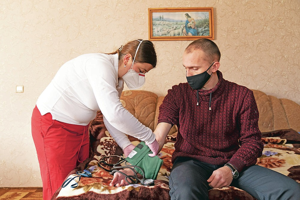 Dr. Viktoria Mahnych, wearing face mask against coronavirus, measures a patient's with COVID-19 pressure in Verhovyna village, Ivano-Frankivsk region of Western Ukraine, Wednesday, Jan. 6, 2021. Ukraine is struggling to contain the coronavirus pandemic that has inundated its overburdened medical system, as Dr. Viktoria Mahnych goes door to door providing much needed help to patients.(AP Photo/Evgeniy Maloletka)