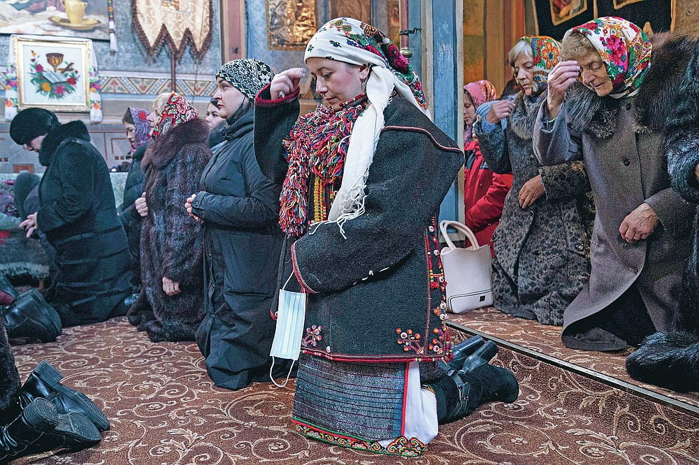 """Dr. Viktoria Mahnych, wearing a Hutsul's traditional colorful clothes, crosses herself holding a face mask in her hand because other worshippers forced her to take off her mask """" in order not to remind about the contagion"""" in the Holy Trinity church during the Orthodox Christmas celebration in Iltsi village, Ivano-Frankivsk region of Western Ukraine, Thursday, Jan. 7, 2021. Mahnych fears that a lockdown in Ukraine came too late and the long holidays, during which Ukrainians frequented entertainment venues, attended festive parties and crowded church services, will trigger a surge in new coronavirus infections. (AP Photo/Evgeniy Maloletka)"""