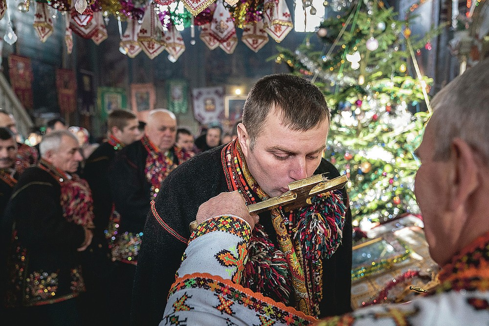 An ethnic Hutsul man, an ethnic group spanning parts of western Ukraine, wearing traditional colorful clothes, kisses a priest's cross during the Orthodox Christmas celebration in the Holy Trinity church in Iltsi village, Ivano-Frankivsk region of Western Ukraine, Thursday, Jan. 7, 2021. Hundreds of maskless parishioners in Verkhovyna lined up at the local church to kiss the icons and the priest's cross during the Christmas service. Ukraine is struggling to contain the coronavirus pandemic that has inundated its overburdened medical system, as Dr. Viktoria Mahnych goes door to door providing much needed help to patients.(AP Photo/Evgeniy Maloletka)
