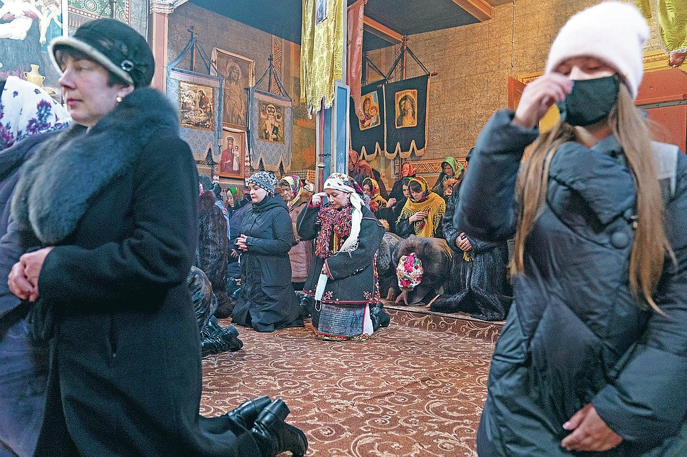 """Dr. Viktoria Mahnych, wearing a Hutsul's traditional colorful clothes, center, crosses herself holding a face mask in her hand because other worshippers forced her to take off her mask """" in order not to remind about the contagion"""" in the Holy Trinity church during the Orthodox Christmas celebration in Iltsi village, Ivano-Frankivsk region of Western Ukraine, Thursday, Jan. 7, 2021. Mahnych fears that a lockdown in Ukraine came too late and the long holidays, during which Ukrainians frequented entertainment venues, attended festive parties and crowded church services, will trigger a surge in new coronavirus infections. (AP Photo/Evgeniy Maloletka)"""