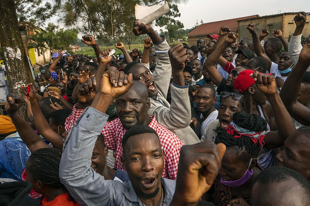 Supporters of leading opposition challenger Bobi Wine cheer as election officials count the ballots after polls closed in Kampala, Uganda, Thursday, Jan. 14, 2021. Ugandans voted in a presidential election tainted by widespread violence that some fear could escalate as security forces try to stop supporters of Wine from monitoring polling stations.(AP Photo/Jerome Delay)