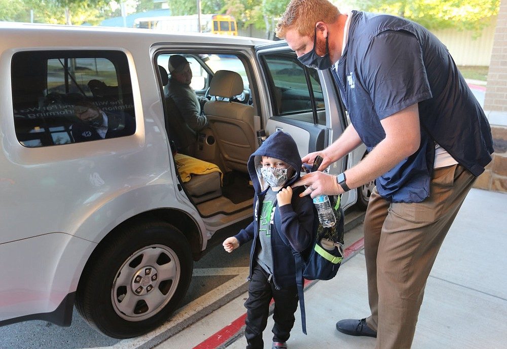John Gourlay, director of development at The New School, helps Logan Patrick, a first grade student, with his back pack Thursday, October 1, 2020, as he enters the school for a day of classes in Fayetteville. Check out nwadg.com/photos for a photo gallery.(NWA Democrat-Gazette/David Gottschalk)
