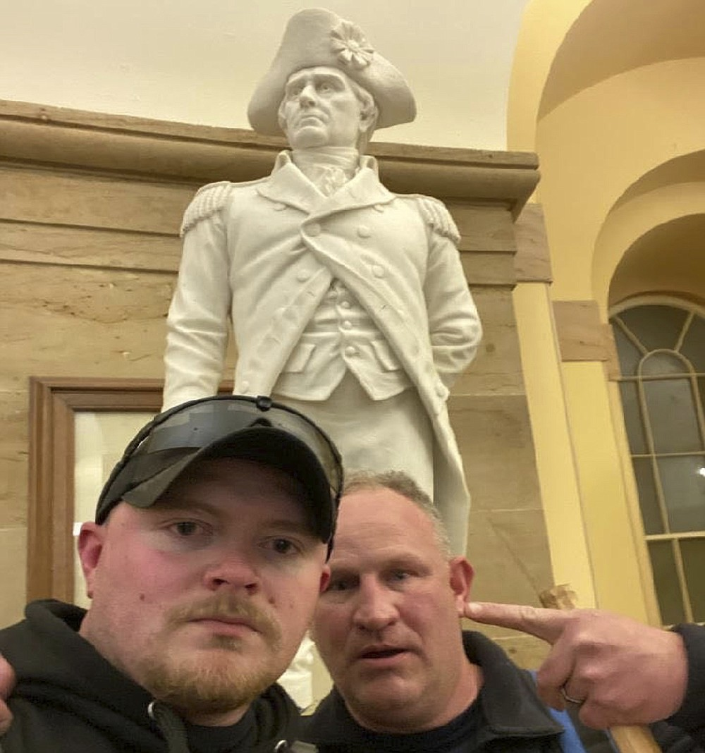 """This Jan. 6, 2021 photo made available by the United States Capitol Police in a complaint and arrest warrant shows Rocky Mount Police Department Sgt. Thomas """"T.J."""" Robertson and officer Jacob Fracker in the Capitol in front of a statute of John Stark, a Revolutionary War officer famous for writing the state motto of New Hampshire, """"Live Free or Die."""" (Courtesy United States Capitol Police via AP)"""