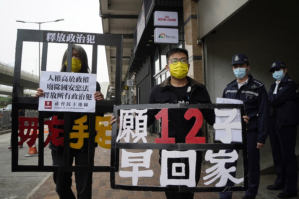 "FILE - In this Dec. 10, 2020, file photo, pro-democracy activists Leung Kwok-hung, left, and Raphael Wong Ho-ming holding placards, demand the release of the 12 Hong Kong activists detained at sea by Chinese authorities as they march to the Chinese central government's liaison office, in Hong Kong. A Chinese lawyer who represented a Hong Kong pro-democracy activist was stripped of his law license on Friday, Jan. 15, 2021,  amid efforts by Beijing to crush opposition to its tighter control over the territory. The placards read ""Never forget our brothers"" and ""Hope 12 Hong Kong activists come home soon."" (AP Photo/Kin Cheung, File)"
