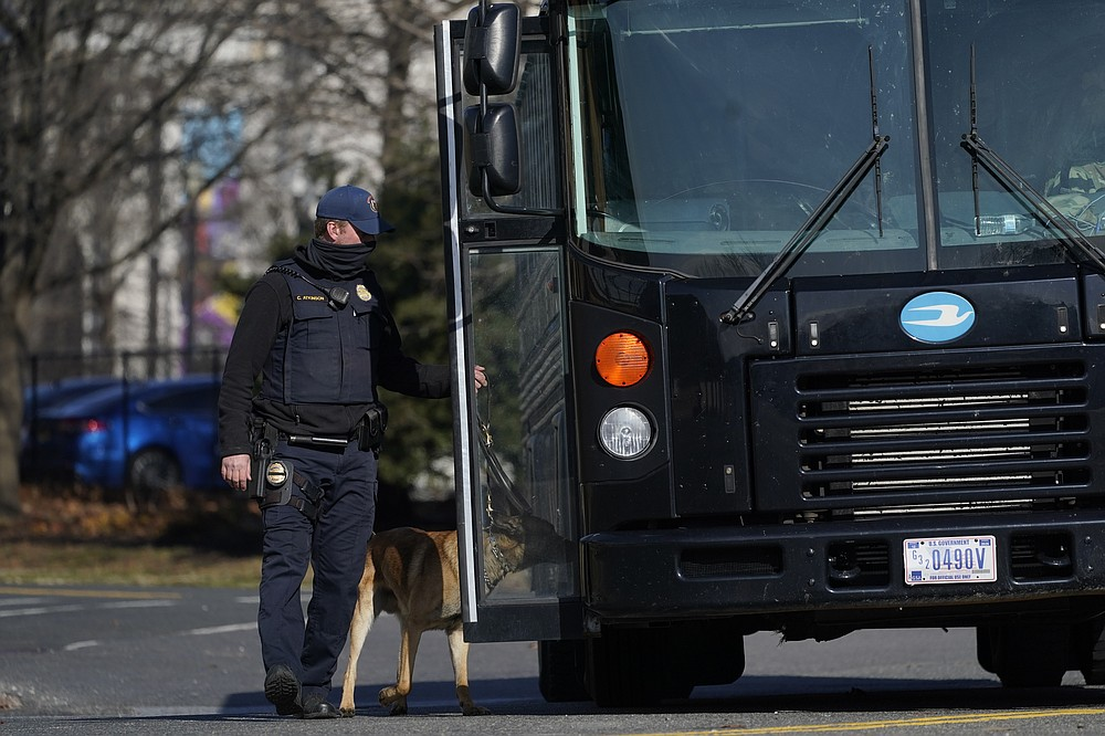 A bomb sniffing dog goes around a bus full of National Guard troops after it arrived at the Capitol, Saturday, Jan. 16, in Washington ahead of the inauguration of President-elect Joe Biden and Vice President-elect Kamala Harris. (AP Photo/Julio Cortez)