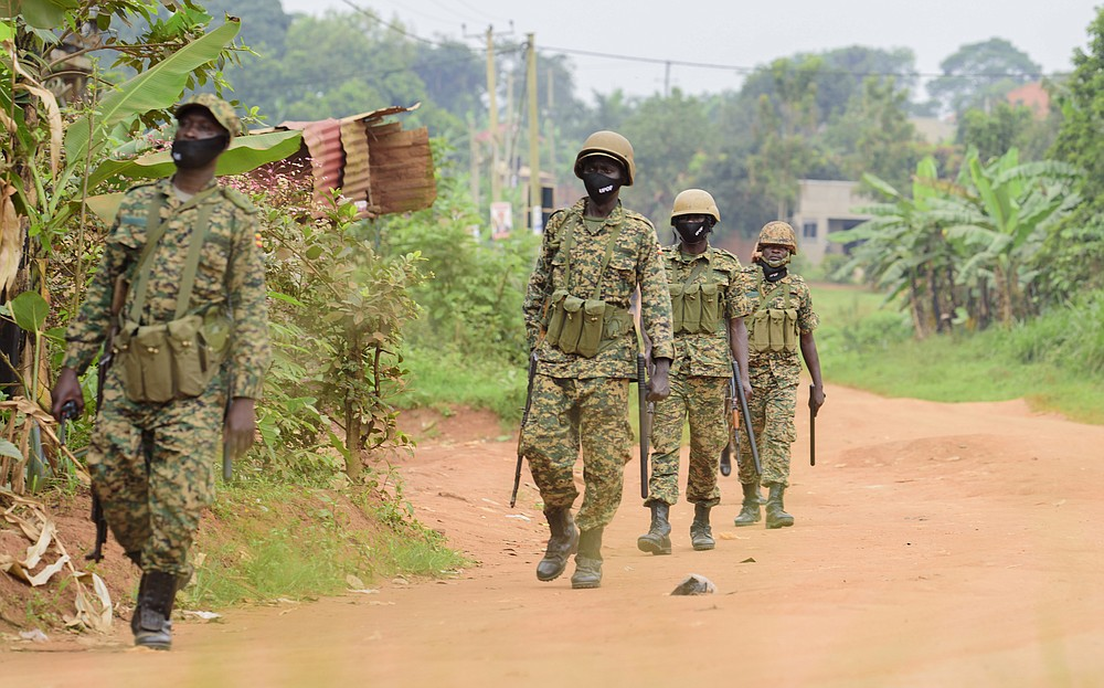 Soldiers patrol outside opposition challenger Bobi Wine's home in Magere, Kampala, Uganda, Saturday, Jan. 16, 2021, after President Yoweri Museveni was declared the winner of the presidential election. Uganda's electoral commission says longtime President Yoweri Museveni has won a sixth term, while top opposition challenger Bobi Wine alleges rigging and officials struggle to explain how polling results were compiled amid an internet blackout. In a generational clash widely watched across the African continent, the young singer-turned-lawmaker Wine posed arguably the greatest challenge yet to Museveni. (AP Photo/Nicholas Bamulanzeki)