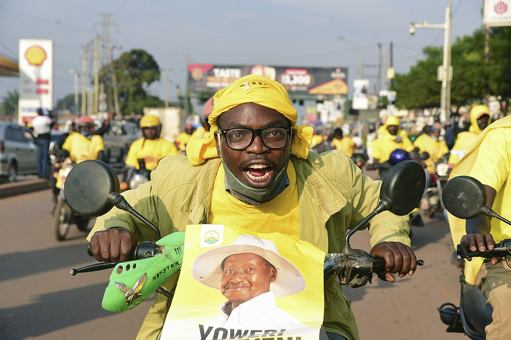 A supporter of Ugandan President Yoweri Kaguta Museveni celebrates in Kampala, Uganda, Saturday Jan. 16, 2021, after their candidate was declared winner of the presidential elections.  Uganda's electoral commission says longtime President Yoweri Museveni has won a sixth term, while top opposition challenger Bobi Wine alleges rigging and officials struggle to explain how polling results were compiled amid an internet blackout. In a generational clash widely watched across the African continent, the young singer-turned-lawmaker Wine posed arguably the greatest challenge yet to Museveni. (AP Photo/Nicholas Bamulanzeki)