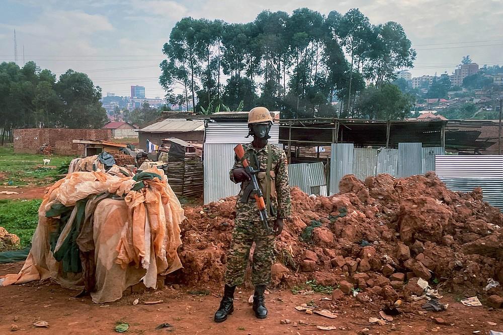 Ugandan security forces guards a checkpoint Kampala, Uganda, Saturday Jan. 16, 2021, after Ugandan President Yoweri Kaguta Museveni was declared winner of the presidential elections.  (AP Photo/Jerome Delay)