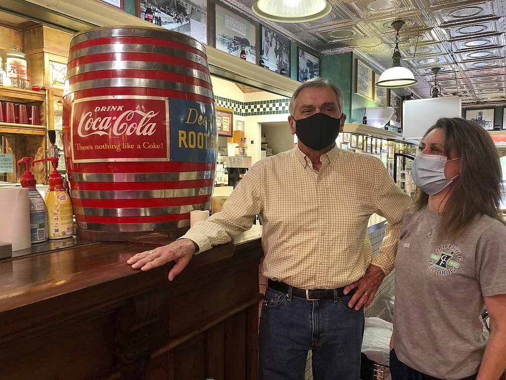 Pharmacists Ric Griffith and his daughter, Heidi Griffith Romero, stand in their family's business Friday, Jan. 15, 2021, in Kenova, W.Va. Griffith & Feil is among 250 mom-and-pop pharmacies in West Virginia helping to vaccinate residents in the quest to banish the coronavirus pandemic. (AP Photo/John Raby)