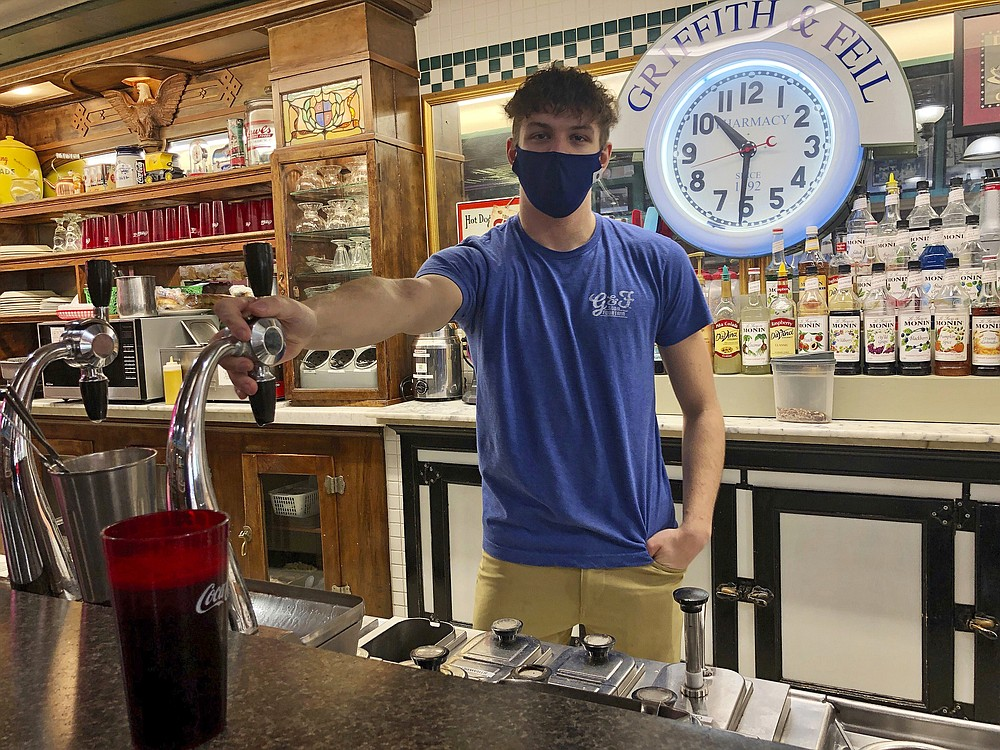 """Parker Elmore works the soda fountain behind the lunch counter at the Griffith and Feil pharmacy Thursday, Jan. 14, 2021, in Kenova, W.Va. Asked if anyone ever called him a soda jerk, a person who runs a soda fountain, Elmore replied, """"Sometimes people come in here and say, 'What's up, jerk?'"""" (AP Photo/John Raby)"""