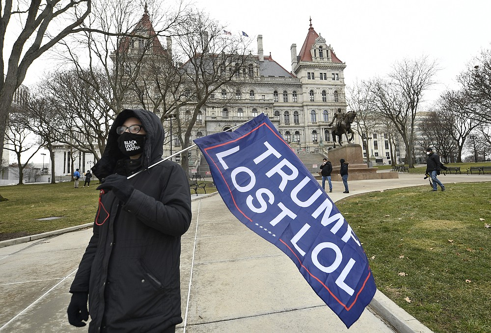 "Christina Janowitz of Guilderland, N.Y., from the group ""All Of Us' holds a flag while counter-protesting a Trump rally ahead of the inauguration of President-elect Joe Biden and Vice President-elect Kamala Harris at the New York State Capitol Sunday, Jan. 17, 2021, in Albany, N.Y. (AP Photo/Hans Pennink)"