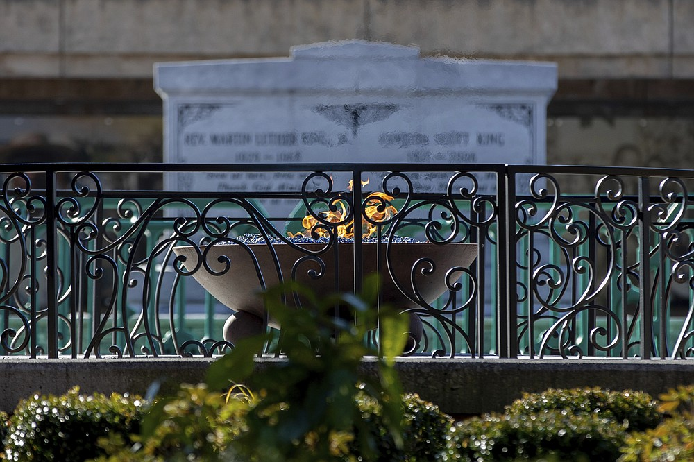 An eternal flame burns at the tomb of the Rev. Martin Luther King Jr. and his wife, Coretta Scott King, on Monday, Jan. 18, 2021, in Atlanta. (AP Photo/Branden Camp)