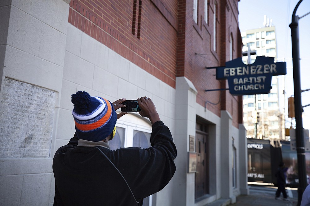 A man takes a photo of the Historic Ebenezer First Baptist Church where Martin Luther King Jr. preached on Monday, Jan. 18, 2021, in Atlanta. (AP Photo/Branden Camp)