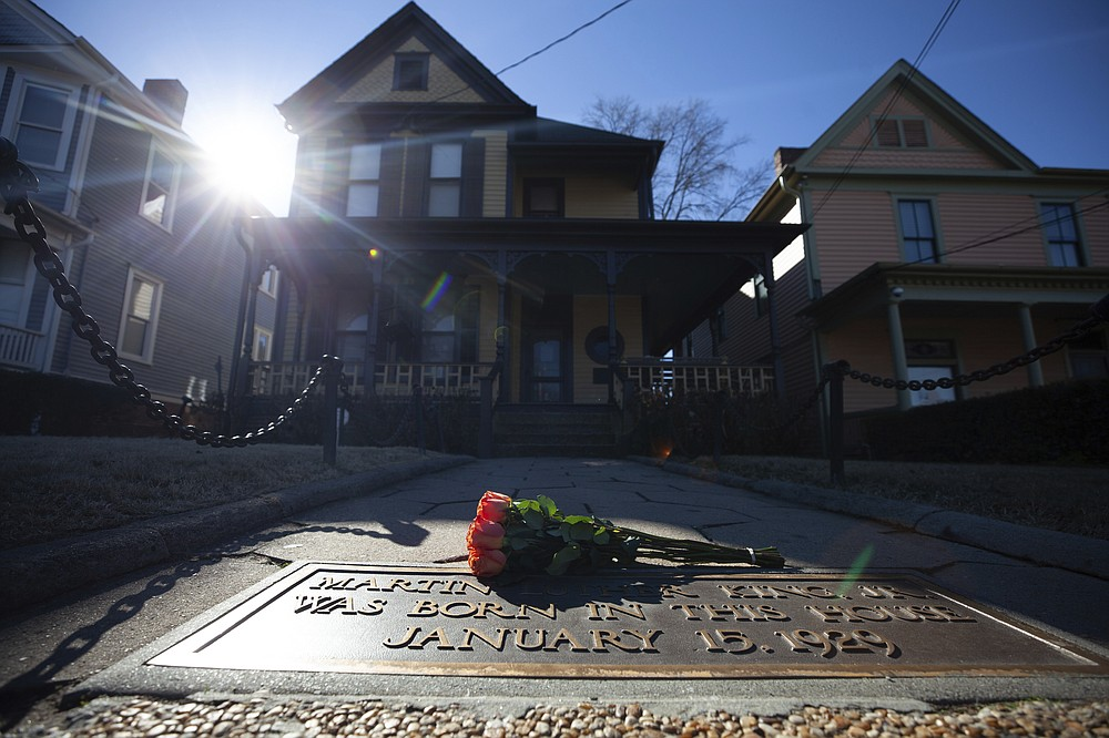 Flowers lay in front of the birthplace of Dr. Martin Luther King, Jr., on Monday, Jan. 18, 2021, in Atlanta. (AP Photo/Branden Camp)