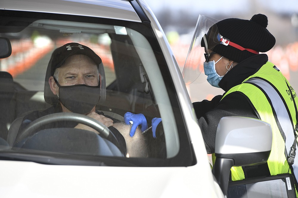 Educator John Cormier of Norwich, Conn., receives a shot from LPN Lizmary Reyes, right, on opening day of the Connecticut's largest COVID-19 Vaccination Drive-Through Clinic Monday, Jan. 18, 2021, in East Hartford, Conn. The former Pratt & Whitney Runway has been converted into a ten-lane, drive-through COVID-19 Mass Vaccination Clinic, with the Pfizer-BioNTech vaccine being administered by Community Health Center, Inc. (CHC). Vaccinations are by appointment only to eligible individuals in Phase 1a and 1b through Connecticut's 211 system or the CDC's Vaccine Administration Management System. (AP Photo/Jessica Hill)