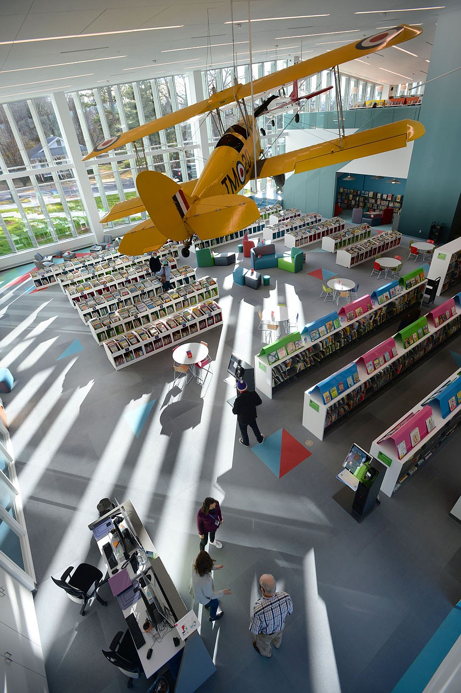 Aircraft hang Tuesday above the children's section of the Fayetteville Public Library on the first day that the library has been open since its renovation and expansion. Voters in 2016 approved a property tax increase to help pay for the nearly $50 million expanded library's construction, which brings the building's size up to about 170,500 square feet. Library administrators opened to the public for the first time since late September, limiting the number of patrons to 200 at a time out of concern for the coronavirus pandemic. Visit nwaonline.com/210120Daily/ for today's photo gallery.  (NWA Democrat-Gazette/Andy Shupe)