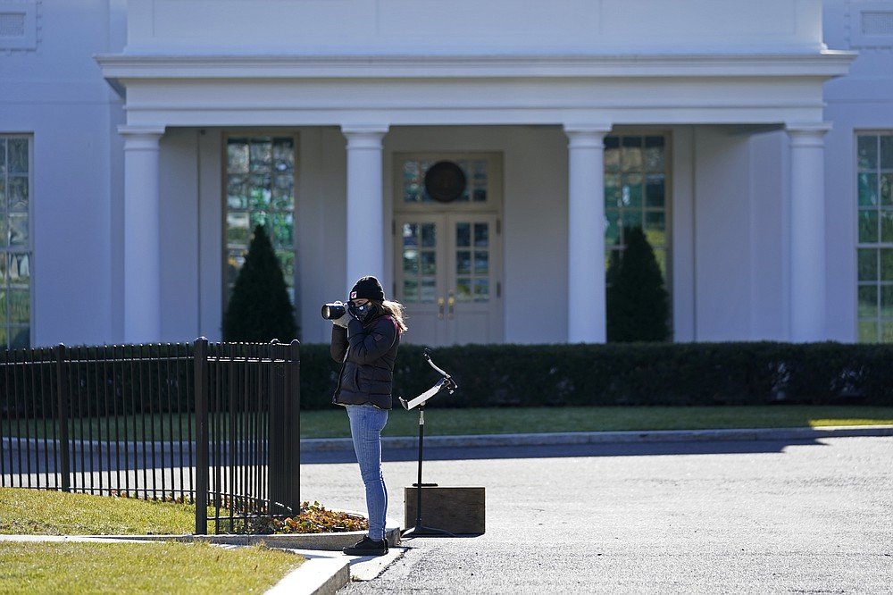 Freelance photographer Allison Dinner photographs workers setting up lights, in front the West Wing of the White House, Tuesday, Jan. 19, 2021, in Washington. On President Donald Trump's last full day in office, there was an eerie quiet, with no public events scheduled, his last event being Jan. 12, seven days earlier. (AP Photo/Gerald Herbert)