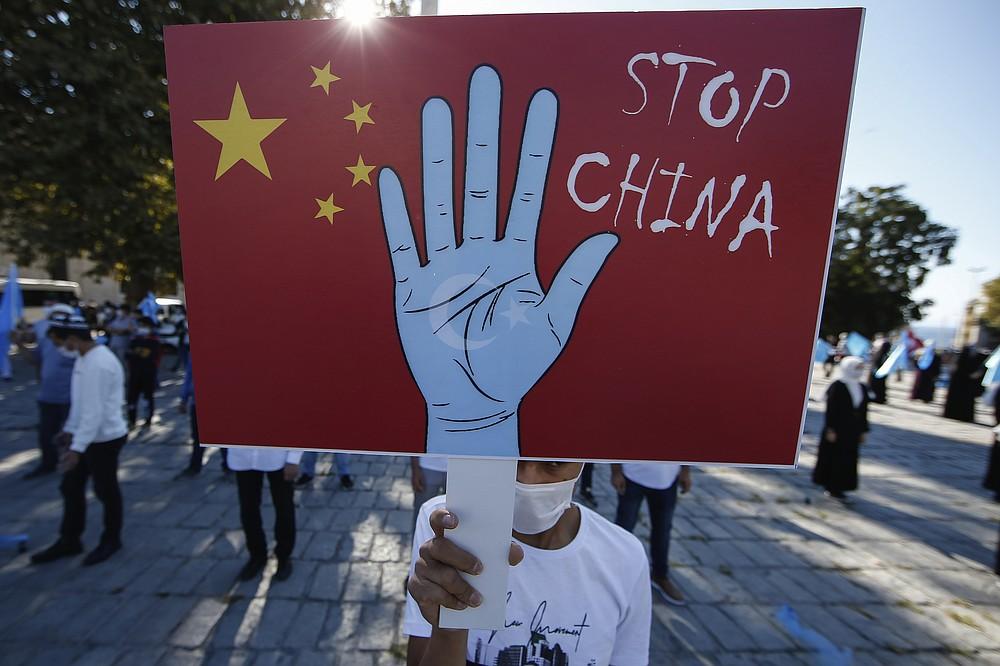 FILE - In this file photo taken Thursday, Oct. 1, 2020, a protester from the Uighur community living in Turkey, holds an anti-China placard during a protest in Istanbul, , against what they allege is oppression by the Chinese government to Muslim Uighurs in far-western Xinjiang province. The accusation of genocide by U.S. Secretary of State Mike Pompeo against China touches on a hot-button human rights issue between China and the West. (AP Photo/Emrah Gurel, File)
