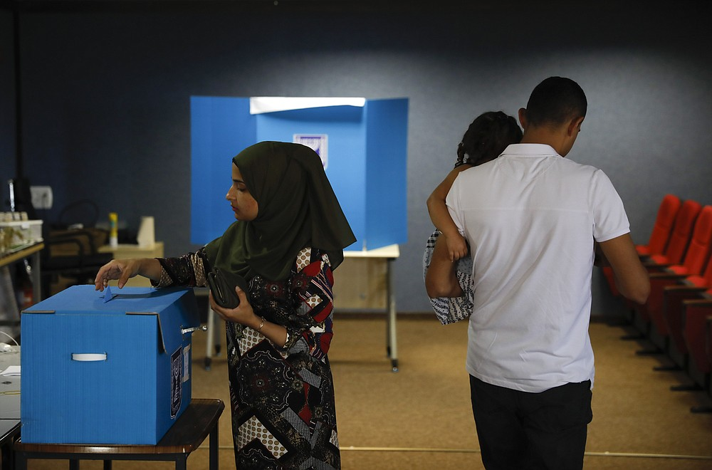 FILE - In this Sept. 17, 2019 file photo, a woman votes in Kfar Manda, an Arab town in Israel. Prime Minister Benjamin Netanyahu, who has spent much of his long career casting Israel's Arab minority as a potential fifth column led by terrorist sympathizers, is now openly courting their support as he seeks reelection in the country's fourth vote in less than two years. (AP Photo/Ariel Schalit, File)