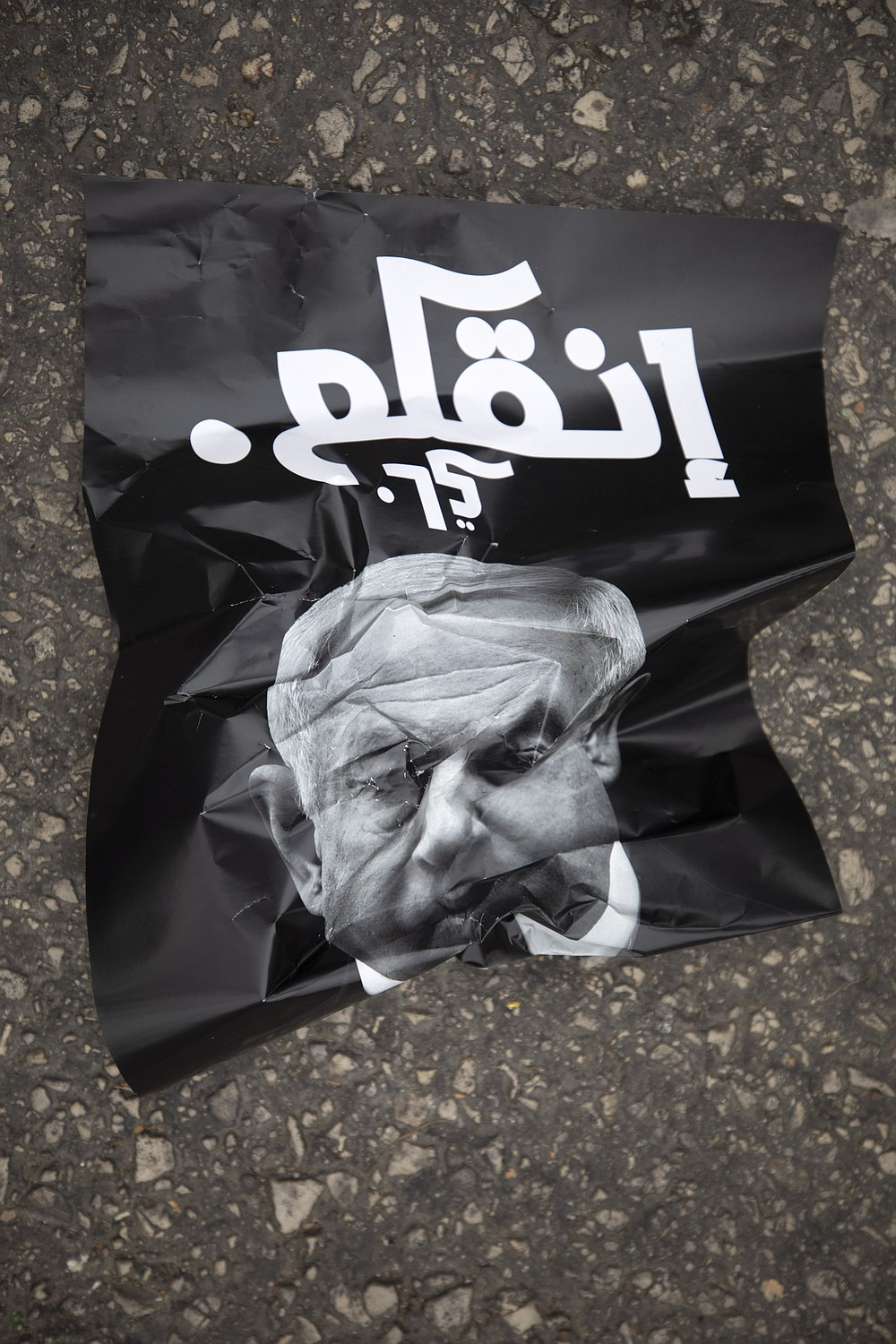 """A poster that reads, """"leave,"""" lies on the ground during a demonstration against a visit by Israeli Prime Minister Benjamin Netanyahu to the northern Arab city of Nazareth, Israel, Wednesday, Jan. 13, 2021. Netanyahu, who has spent much of his long career casting Israel's Arab minority as a potential fifth column led by terrorist sympathizers, is now openly courting their support as he seeks reelection in the country's fourth vote in less than two years. (AP Photo/Sebastian Scheiner)"""