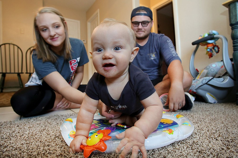 NWA Democrat-Gazette/DAVID GOTTSCHALK Jaylee Kelley and his wife Madalyn play Wednesday, August 1, 2018, with their son Payton inside their apartment in Fayetteville. Teen fathers in northwest Arkansas, like Kelley, have limited parental support resources. The Teen Action and Support Center is working on a teen father mentor group to change that.