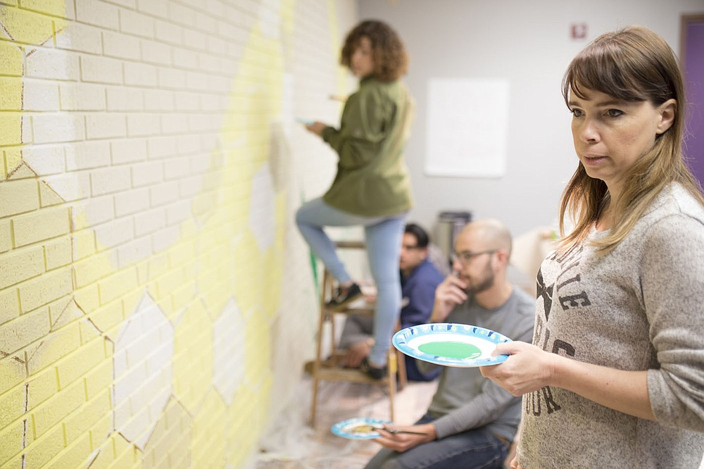 """NWA Democrat-Gazette/CHARLIE KAIJO Eve Smith, artist and director of visual arts at the Arts Center of the Ozarks, looks at the mural she and a group of fellow staff and volunteers are helping to create, Sunday, April 8, 2018 at The Station in Springdale. She created the design for the mural.   Staff and volunteers are painting a mural in preparation for their grand opening on Thursday. The mural, a collaborative effort by the Teen Action & Support Center (TASC) and the Arts Center of the Ozarks will feature native plants from countries represented at The Station including Marshall Islands, Mexico and El Salvador. The goal is to promote an atmosphere of collaboration, unity and growth said Aron Shelton, director of the Teen Action & Support Center.   The Station provides teens a space for creative outlets. The youth can work on robotics projects, spoken word and performance art and fine arts in a collaborative environment.   """"The goal is to provide a collaborative model for removing barriers to teens success and empowering teens to take action in their own lives and communities,"""" Shelton said."""