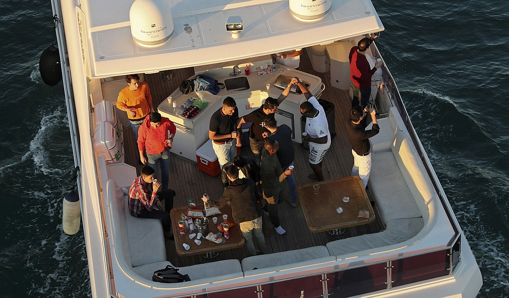 Tourists party on a yacht in Dubai, United Arab Emirates, Tuesday, Jan. 12, 2021. Since becoming one of the world's first destinations to open up for tourism, Dubai has promoted itself as the ideal pandemic vacation spot. With peak tourism season in full swing, coronavirus infections are surging to unprecedented heights, with daily case counts nearly tripling in the past month, but in the face of a growing economic crisis, the city won't lock down and can't afford to stand still. (AP Photo/Kamran Jebreili)
